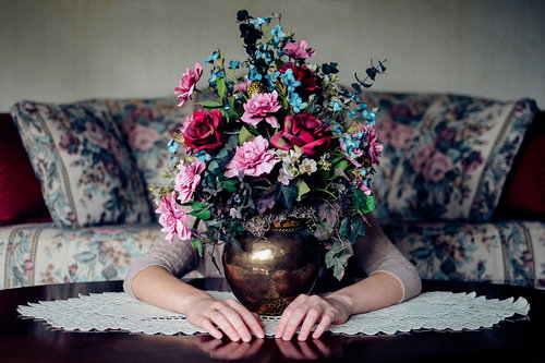 Image of flowers in a vase on a table, a woman sits behind the vase, her face and head concealed by the flowers, with arms wrapped around the base.