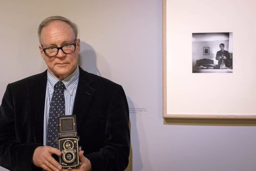 Picture of an older man in a suit holding an old model camera