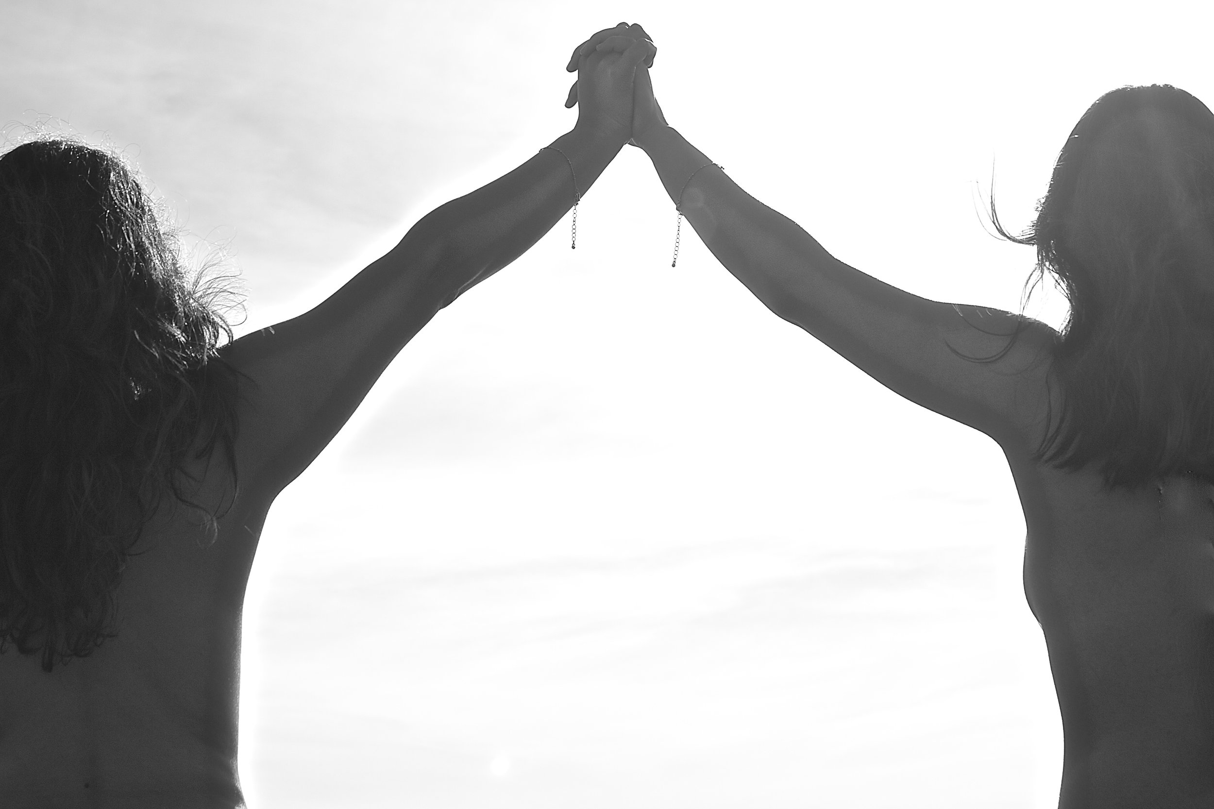 Image of two women holding hands while facing into a white abyss