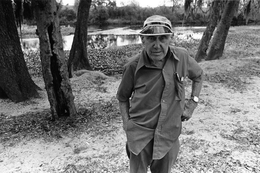 An old man in a wooded park wearing a visor and looking at the camera
