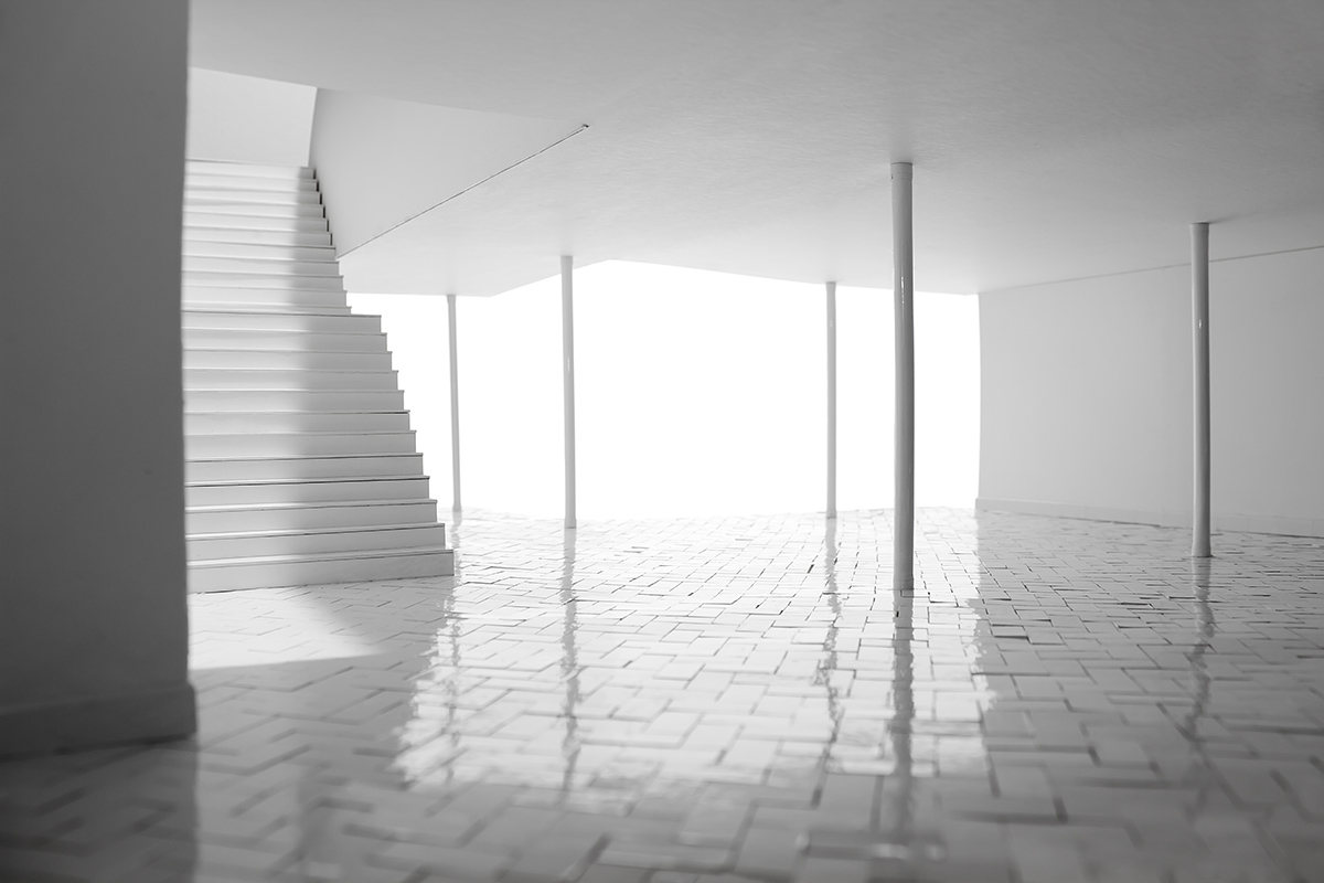 The interior of a model, all white with shiny reflective tile, there is a staircase to the left
