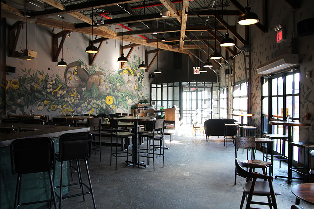 The Taproom - Our bar area features 20' ceilings adorned with reclaimed barn wood beams and a modern, industrial loft-like feel. The huge original mural is by artist, Pixel Pancho, featuring flowering botanicals, bringing the outdoors in. This 3000 square foot space overlooks the outdoor deck and offers flexible seating options, including a mix lounge areas, hightop tables, farmhouse dining tables and bar seating.