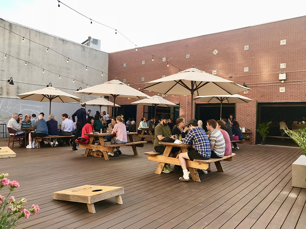The Outdoor Deck - This seasonal outdoor space is perfect for your spring, summer and early fall events. With its wood picnic tables, umbrellas and decorative string light canopy, it's perfect for a baby shower brunch, an evening barbeque, casual dinner, or even a relaxed wedding ceremony. This 2500 square foot patio is dog-friendly and offers entertainment, like a corn hole game, oversized Jenga set and a fully stocked toy box for any children on your guest list. Just off the deck is a 3000 square foot, paved parking lot, perfect for hosting food trucks, or other outdoor entertainment, like a jazz or bluegrass band for your outdoor events.