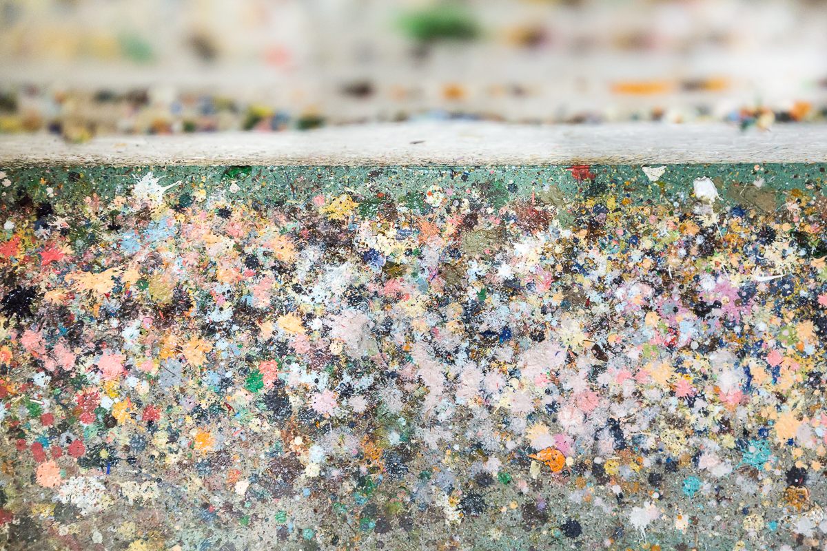 The colorful paint drippings under the spot where Liz paints.