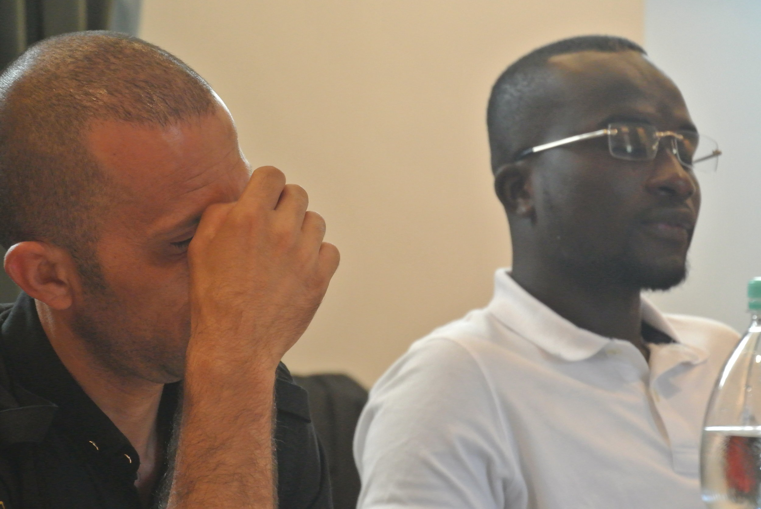 Walid grips his brow while listening to Bakary. The Embassy of Switzerland, Rome. 11 June 2018.