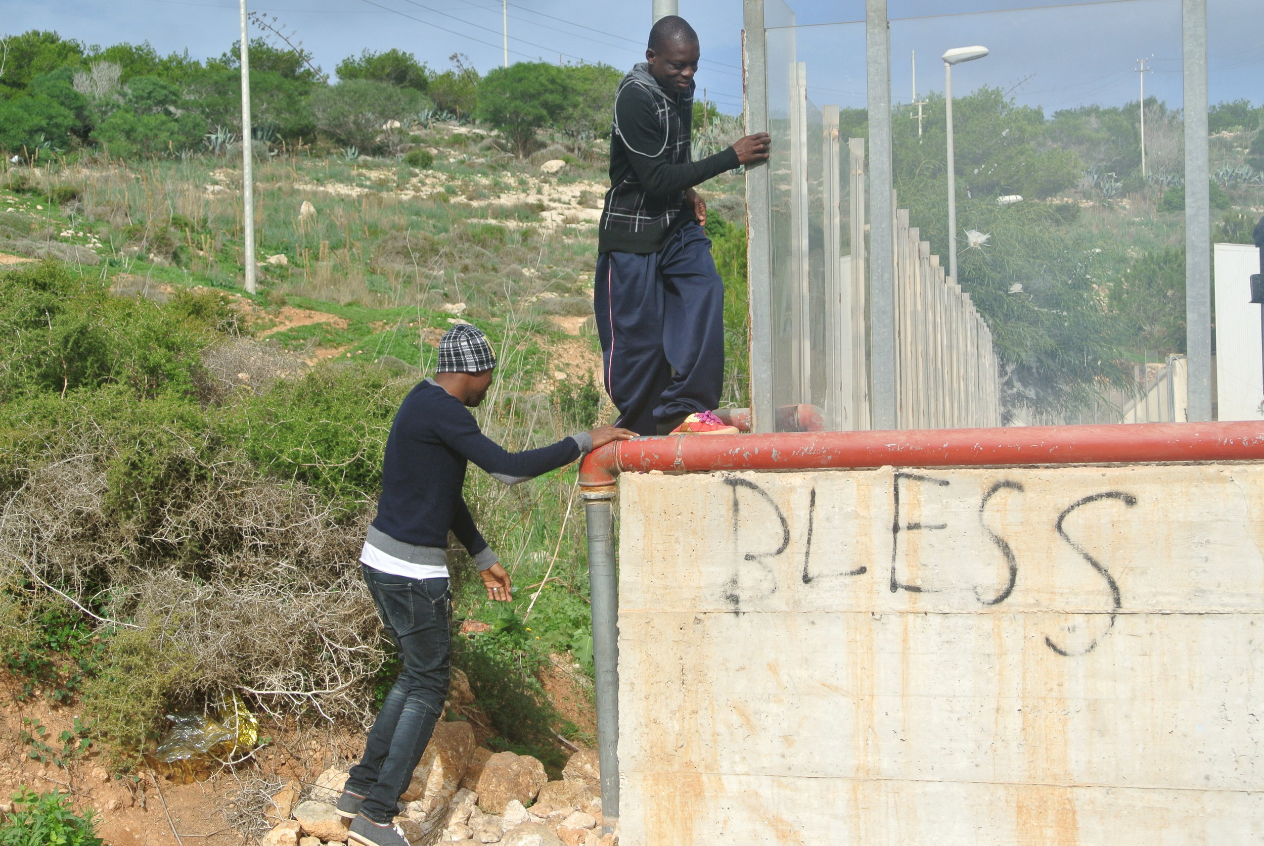 Migrants climb the outer wall to enter the hotspot. Lampedusa, Italy; November 2016. © Pamela Kerpius.