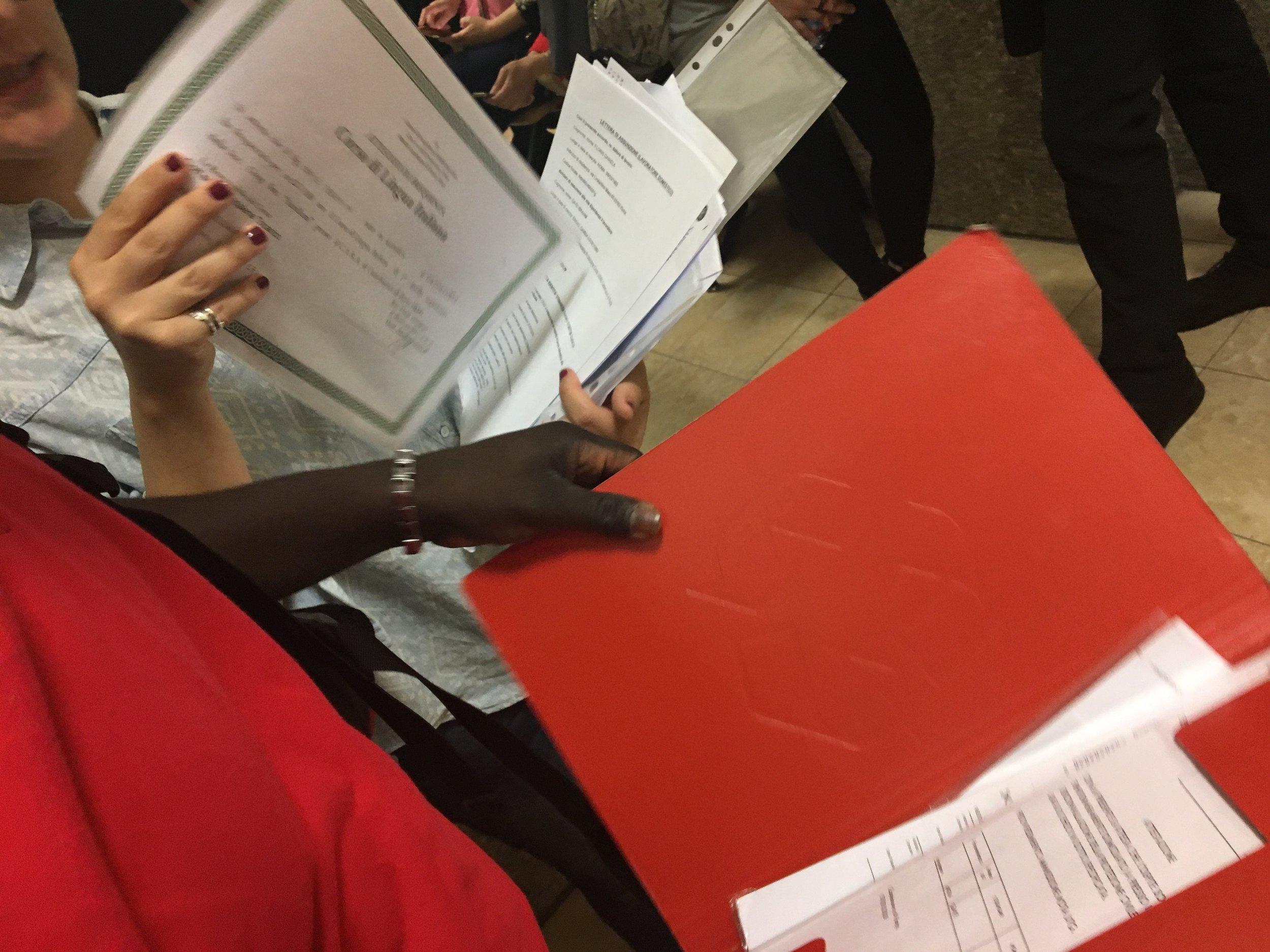 Pazi and his teacher organize his paperwork before seeing the judge. Rome, Italy; 24 April 2018. © Pamela Kerpius