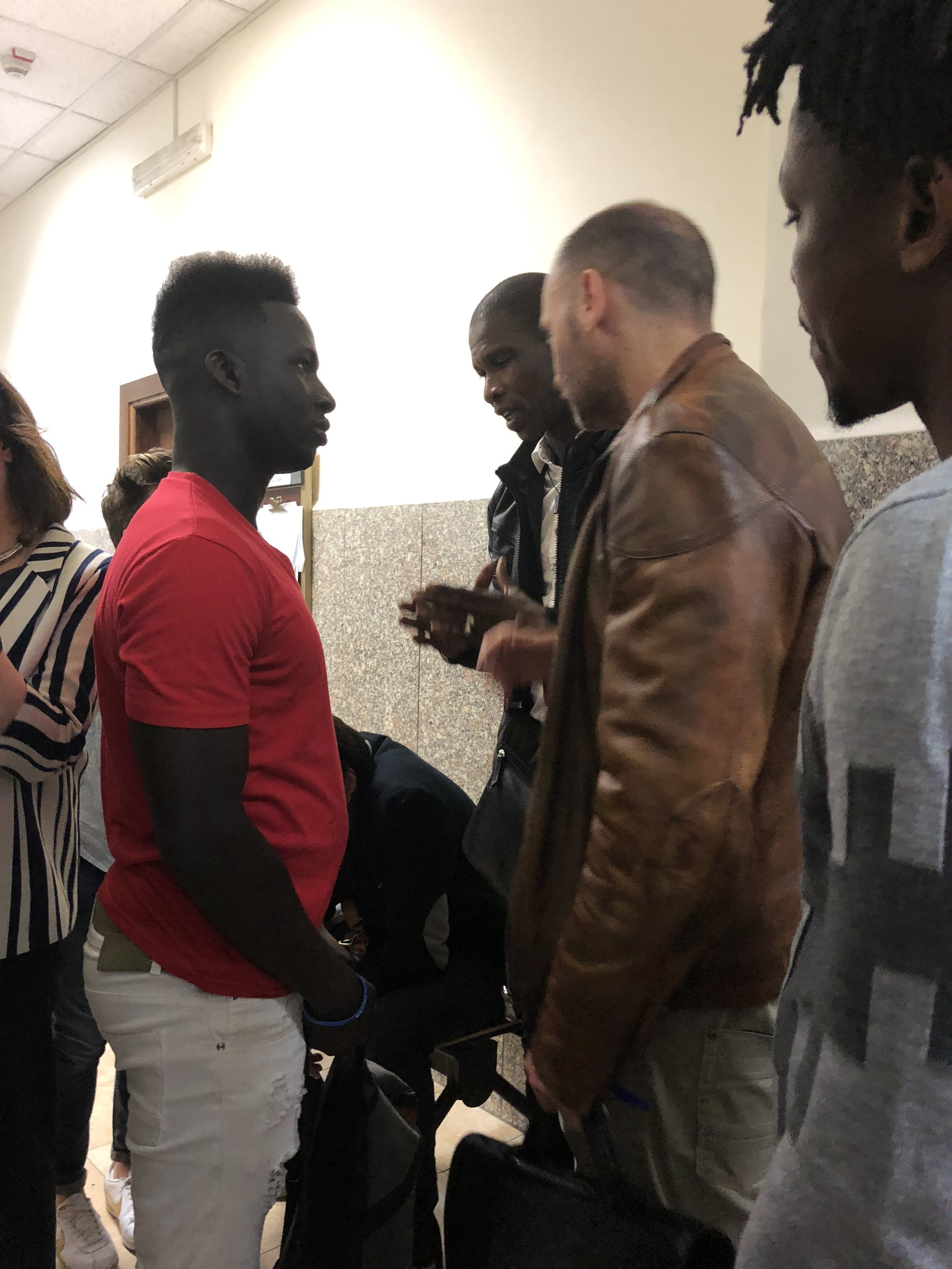 Pazi consulting with his lawyer, at left, in the hectic corridor. Rome, Italy; 24 April 2018. © Pamela Kerpius