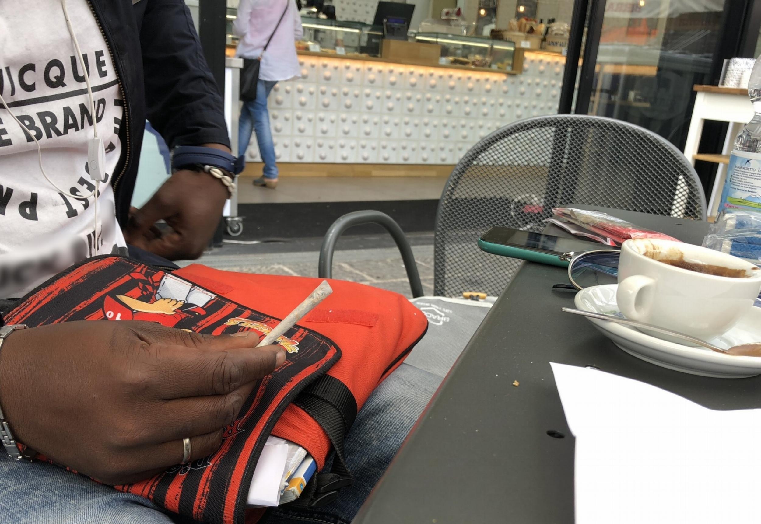 Yoro rolls his cigarette. Naples, Italy; May 2018. © Pamela Kerpius