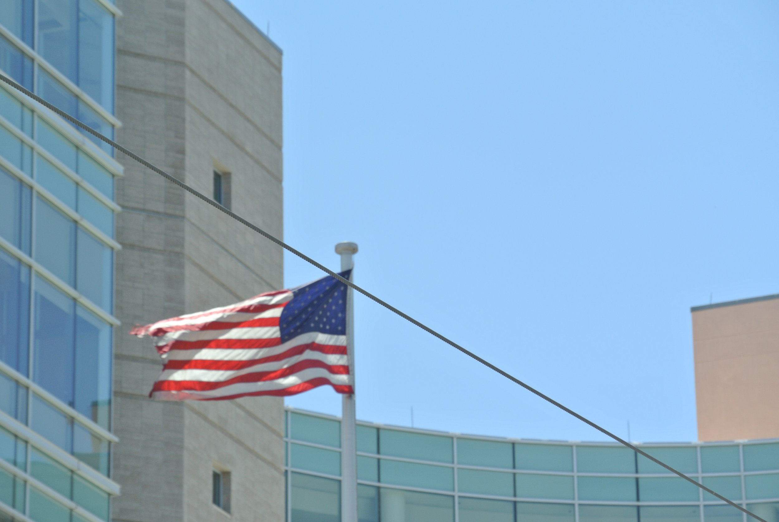 Desert gusts tear at the flag outside of the United States District Court building. Tucson, Arizona; 17 May 2019. ©Pamela Kerpius