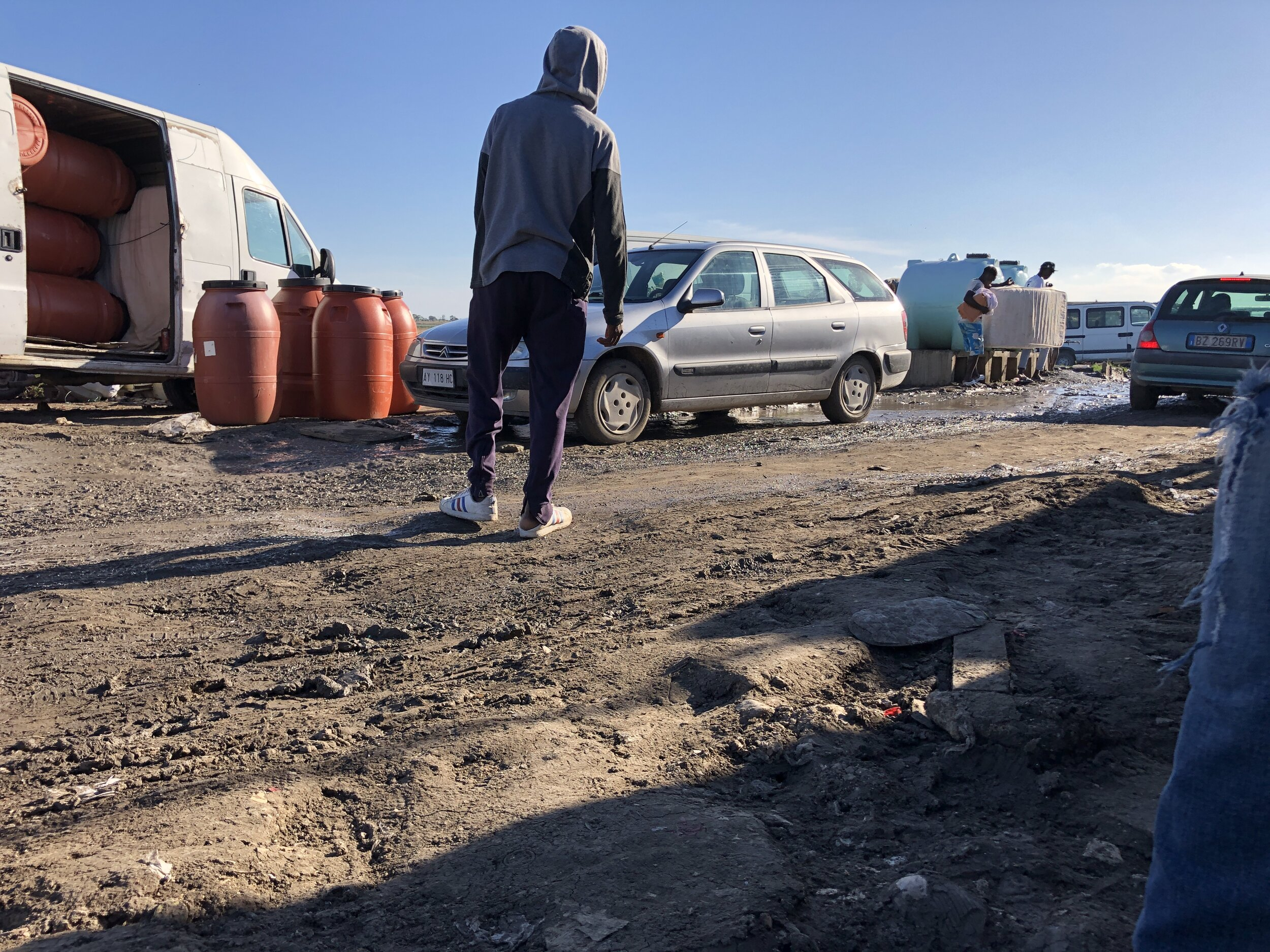 Muddy streets beside the water tanks people use to wash in Gran Ghetto. Foggia, Italy. 8 October 2019. ©Pamela Kerpius