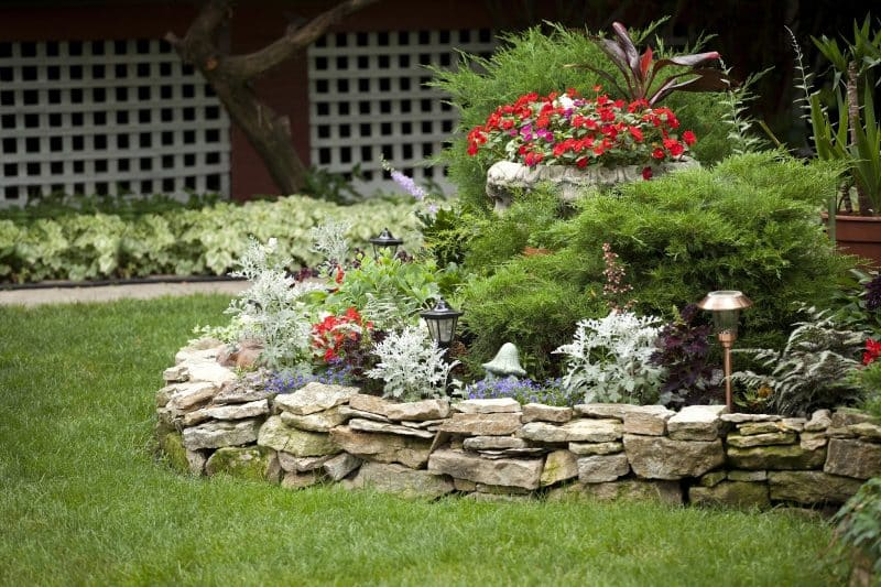 garden-path-resin-strip-edging-with-variety-of-perennial-foliage-in-flat-bed-and-raised-bed-with-dry-stacked-stone-edging-and-red-ti-plant-in-a-decorative-planter-and-brass-outdoor-lanterns-w.jpg