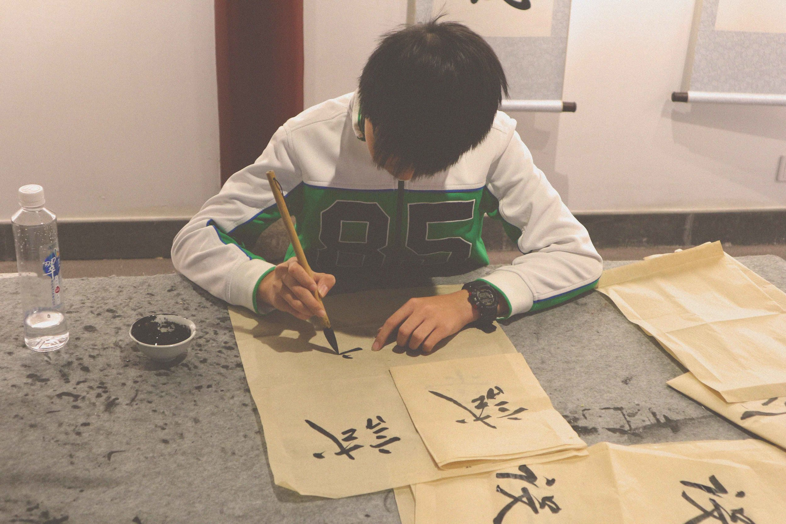 One of the students practicing calligraphy in the Old Town