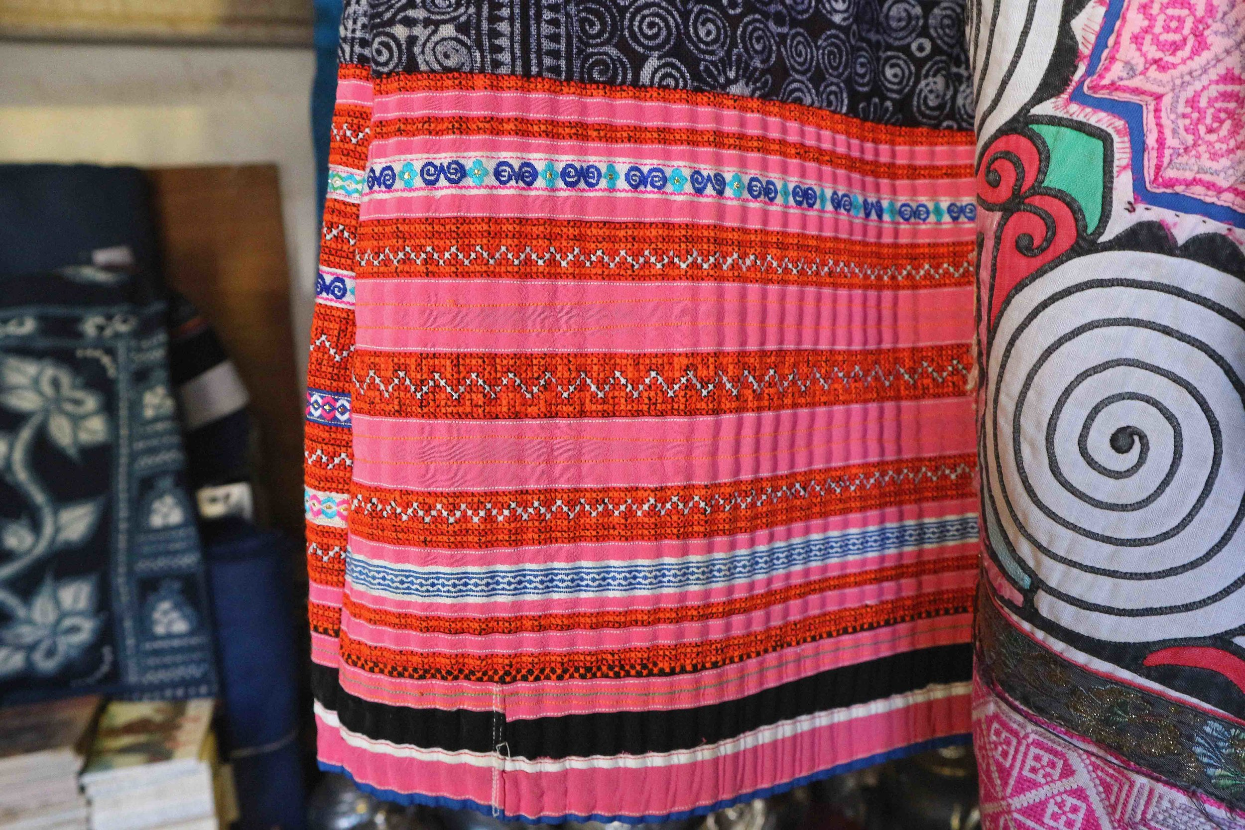 Newly produced clothing from the Miao minority, the cross stitching is done by hand but is quick to produce.  It is typical to find this embroidery detail on the hem of a batik print garments like this one