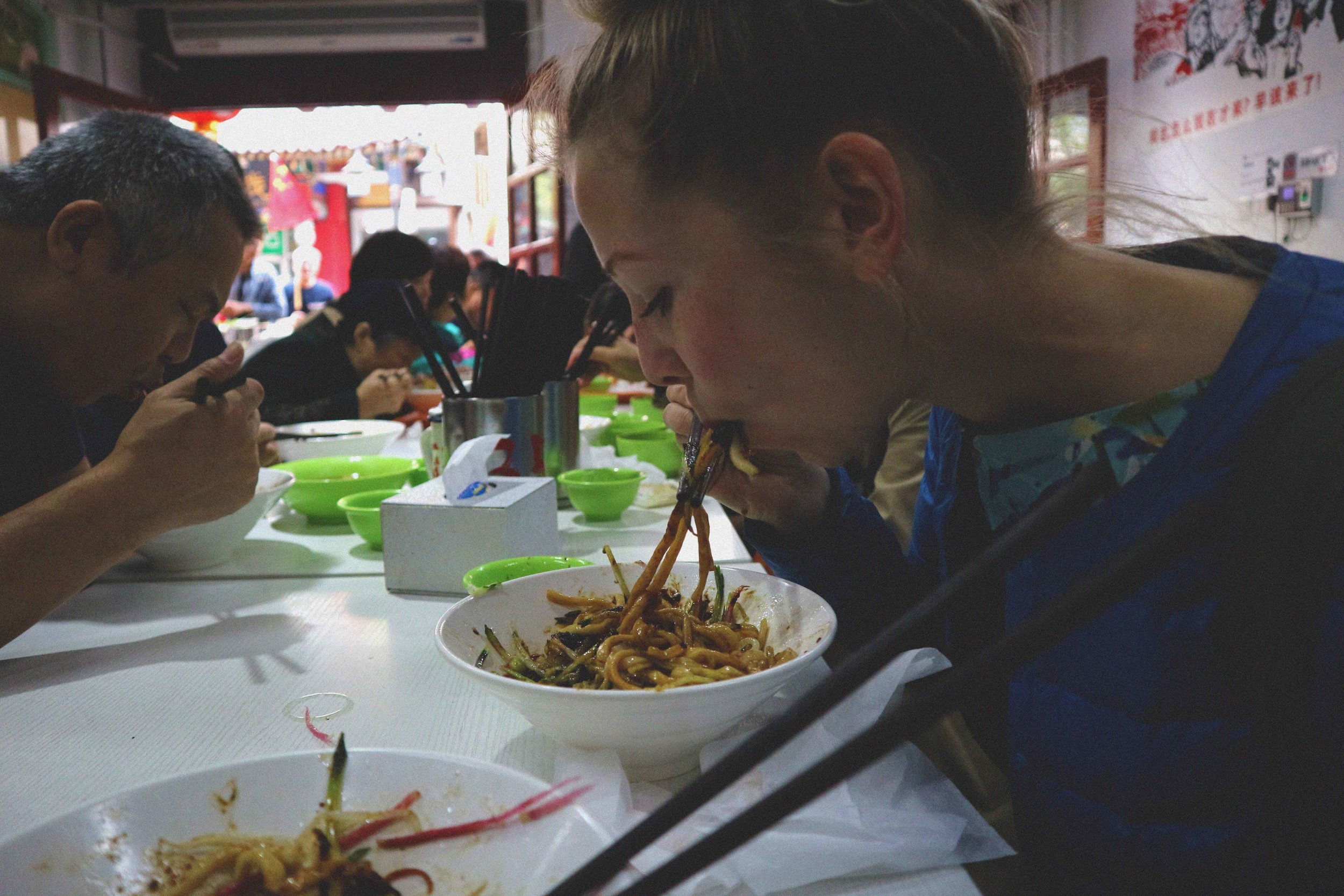 Ali munching on noodles in a traditional noodle kitchen