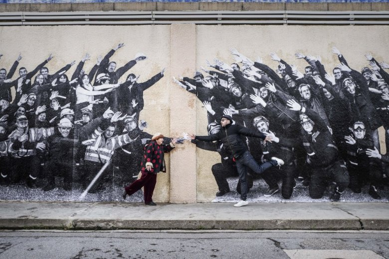 visages-villages-2017-002-agnes-varda-and-jr-reaching-across-wall-with-grafitti.jpg