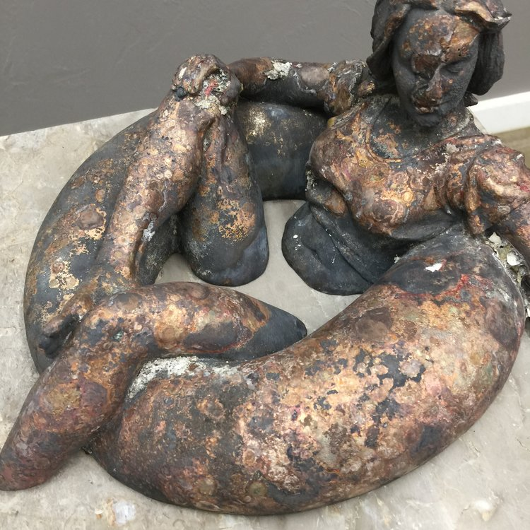 As it was found in the ashes. Severely oxidized, surface wrinkles, glass meted into the bronze in several areas, and the entire piece warped and bowed from the heat.