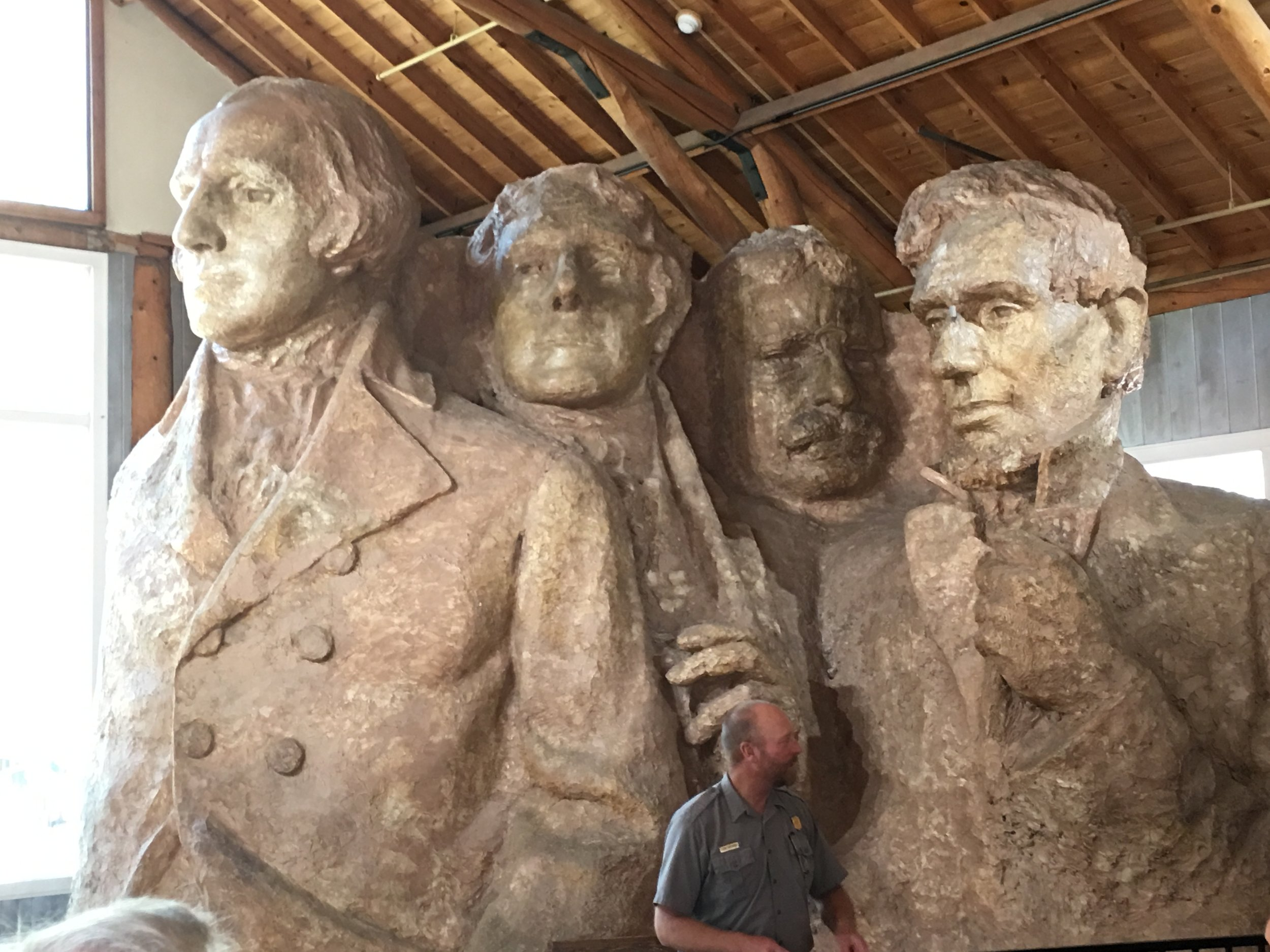 Originally the plan was to carve the Presidents head to waist as shown in the picture of the plan model. Borglum and the team to were forced reduce the scope by funding constraints and the result is the heads we see today. there was even an attempt to add Susan B. Anthony to the project but again lack of funding got in the way.