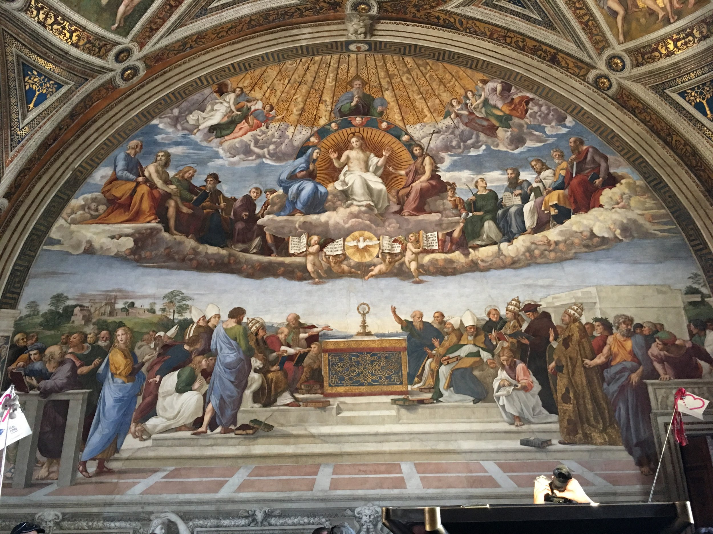 In Raphaels' Disputation of the Holy Sacrament, located in the room Stanza Della Segnatura of Vatican City we see Jesus in the scene depicting both the heavens and earth.  Jesus, bathed in light is located just below the Father God and above the burning light of the Holy Spirit.  Forty days after his resurrection, according to the Gospel of Luke, Jesus ascends into heaven where he takes his place beside the Father God as the advocate for all of mankind.