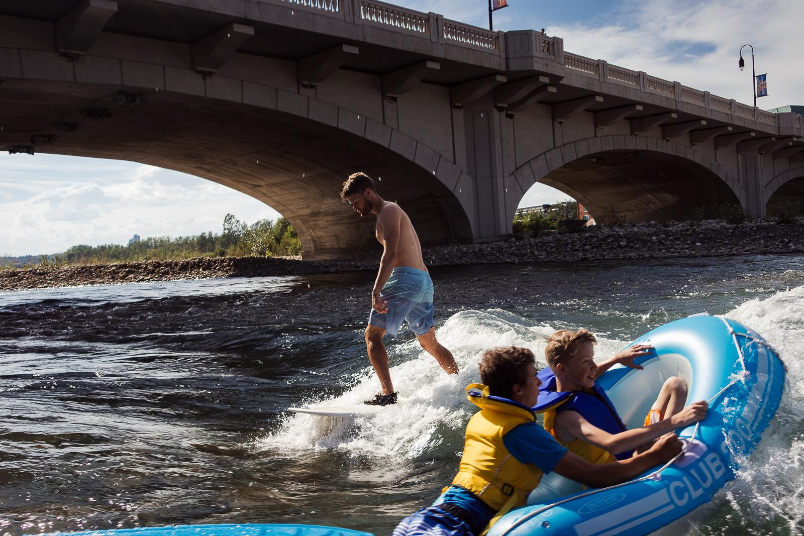Rafting kids and a surfer at 10th Street Wave in Calgary