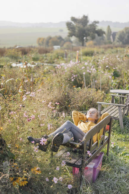 focused_177236038-Young-woman-relaxing-cottage-garden.jpg