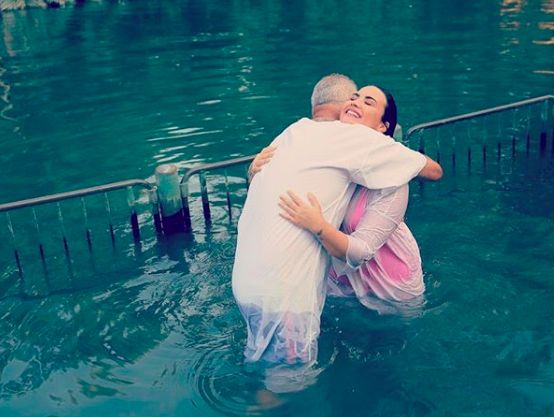 The songstress in complete bliss as she hugs the man who baptized her. via  @ddlovato