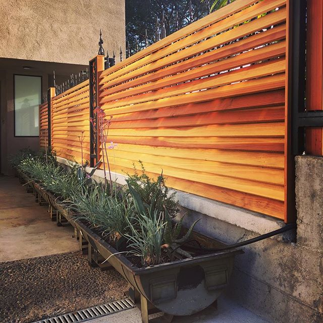 Custom #redwood #louvered #fence and #vintage military #bomb cases repurposed as #planters. One of many design components of a major project of mine nearing completion. #louvers #redwoodfence #customwoodwork #recycle #reuse #upcycle