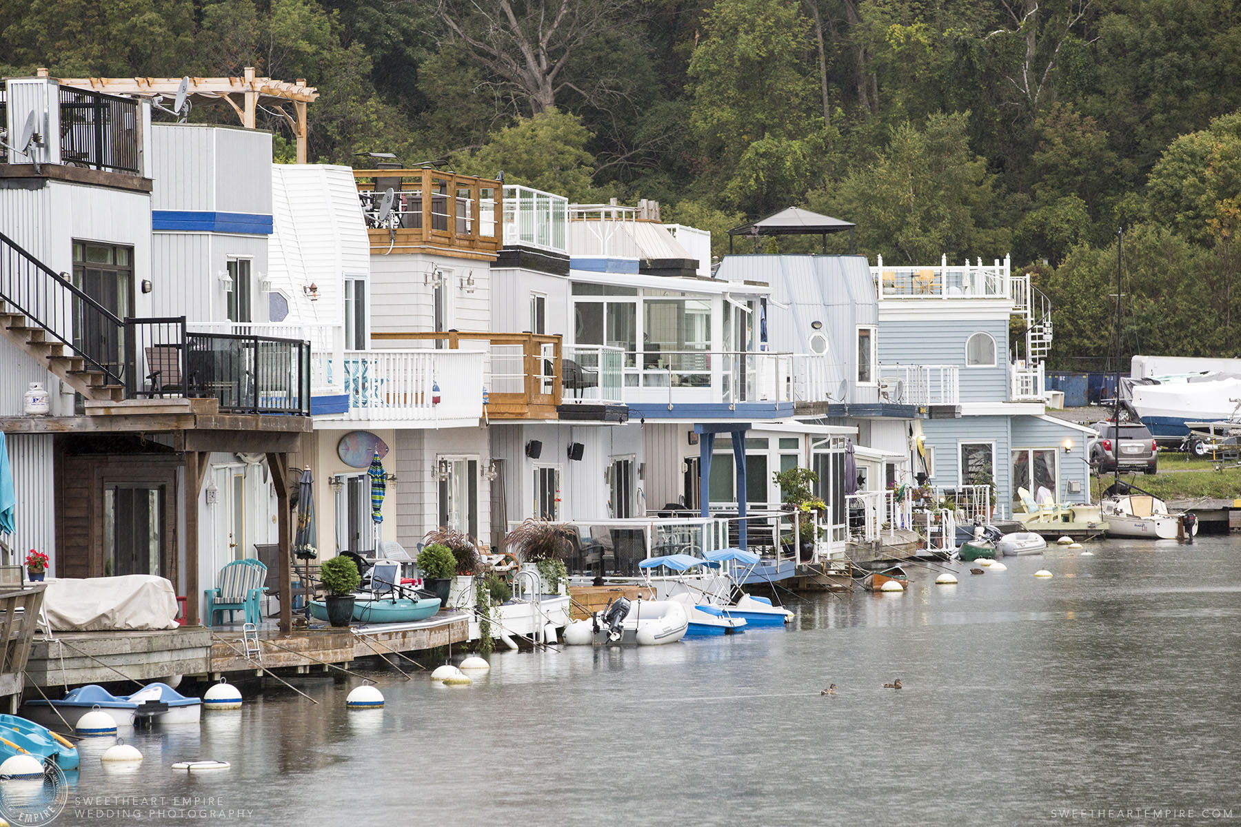 A row of houseboats in nautical-colours, at the Bluffers Park Marina, with the greenery of Scarborough Bluffs rising off in the background, on a rainy day.