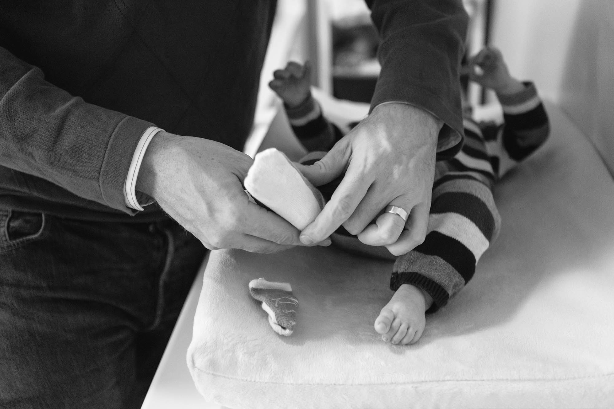 Dad changing babys tiny socks.jpg