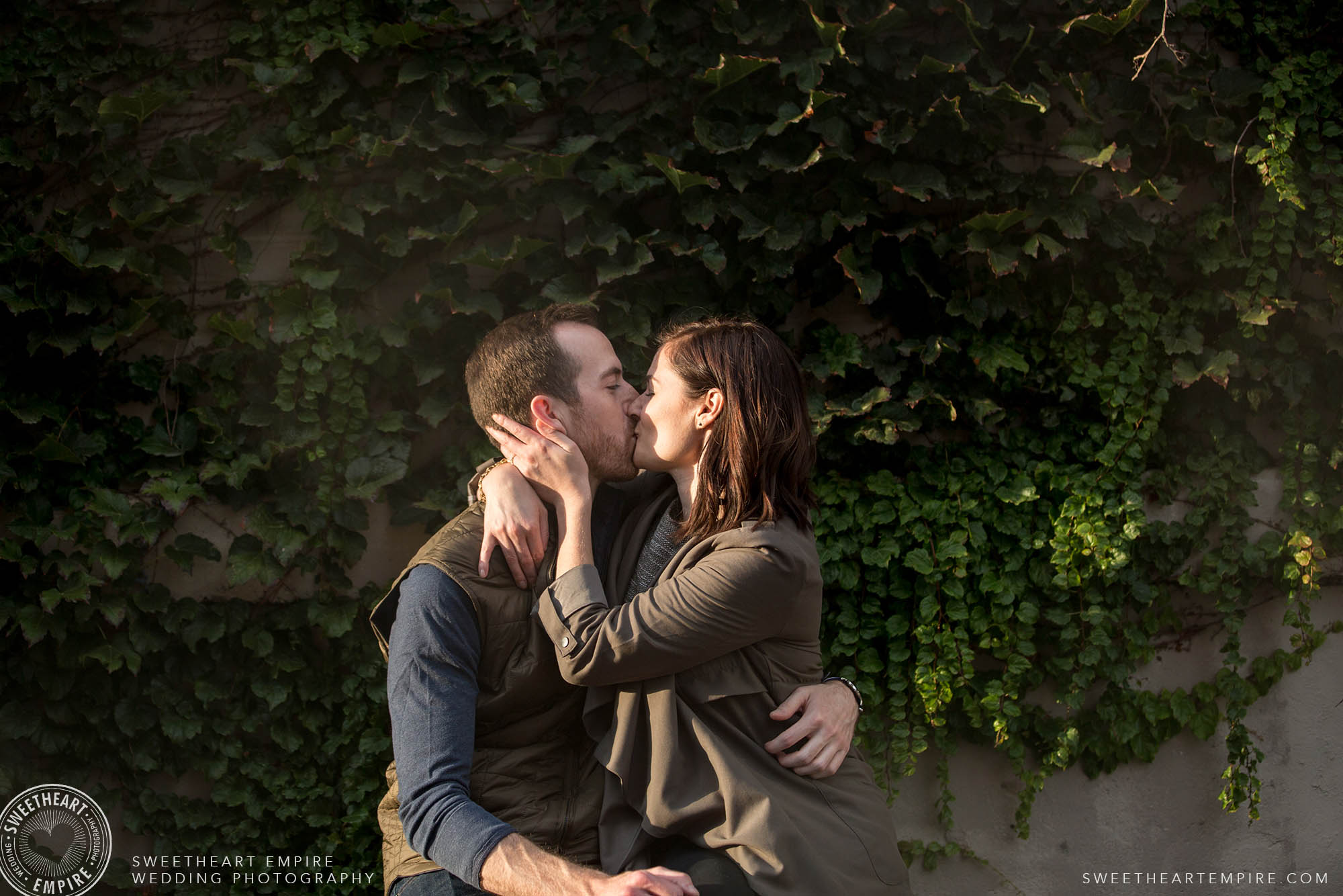Couple kissing in the sun in front of an ivy wall, Leslieville engagement photos