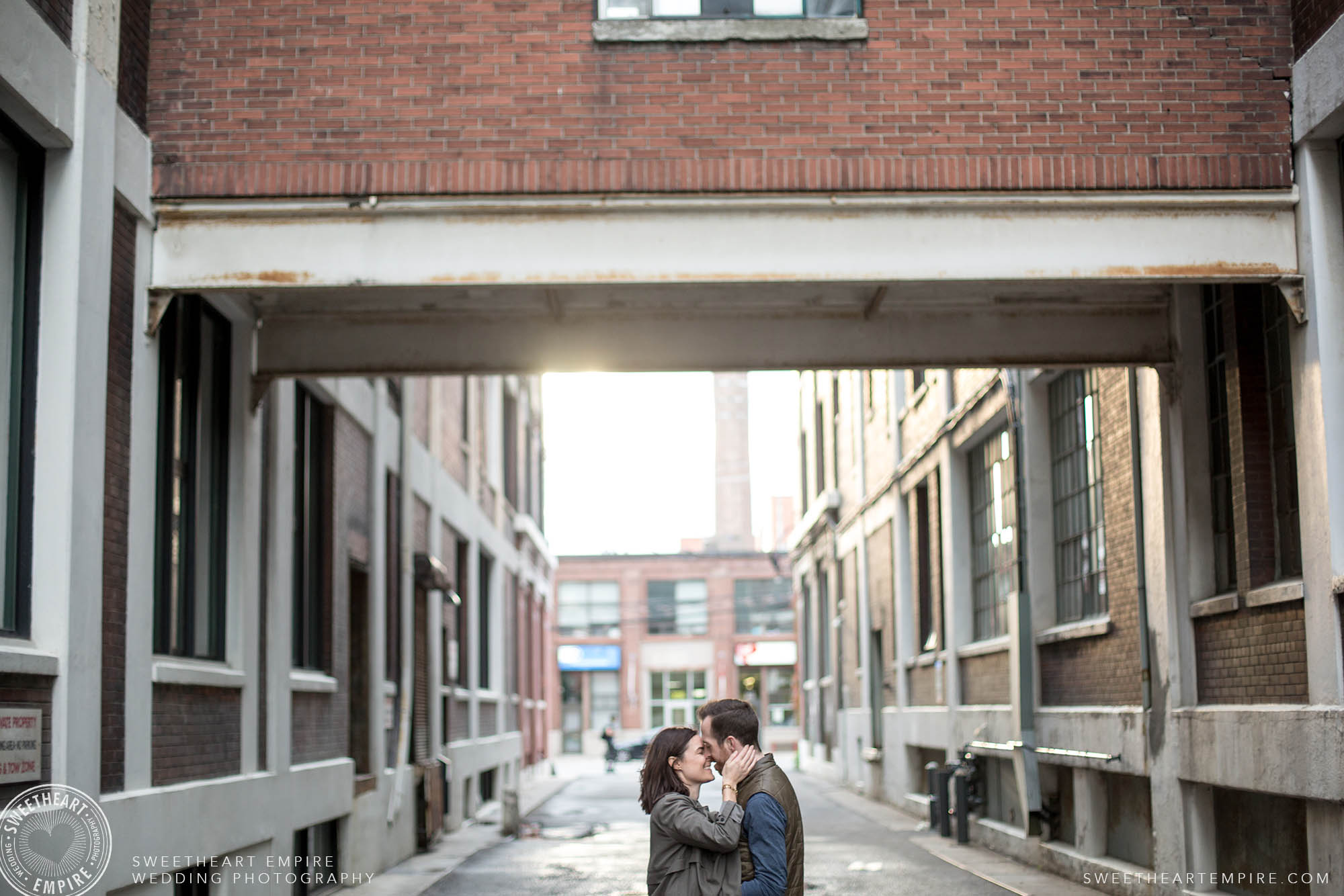 Couple kissing lovingly in an alleyway, Leslieville engagement photos