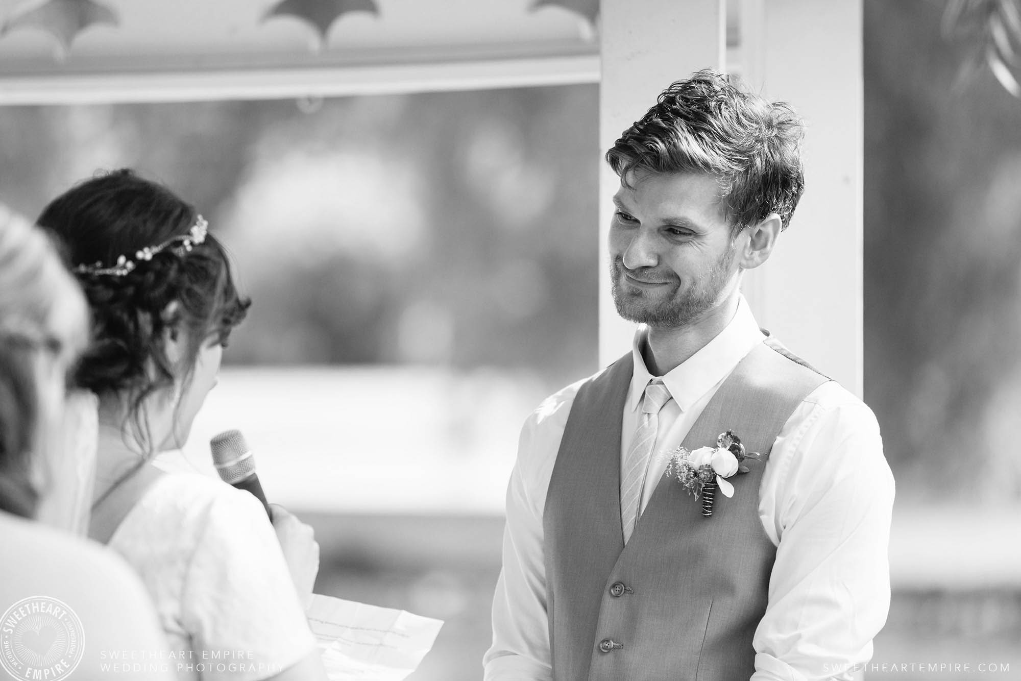 Teary-eyed groom listening to his bride say her vows.