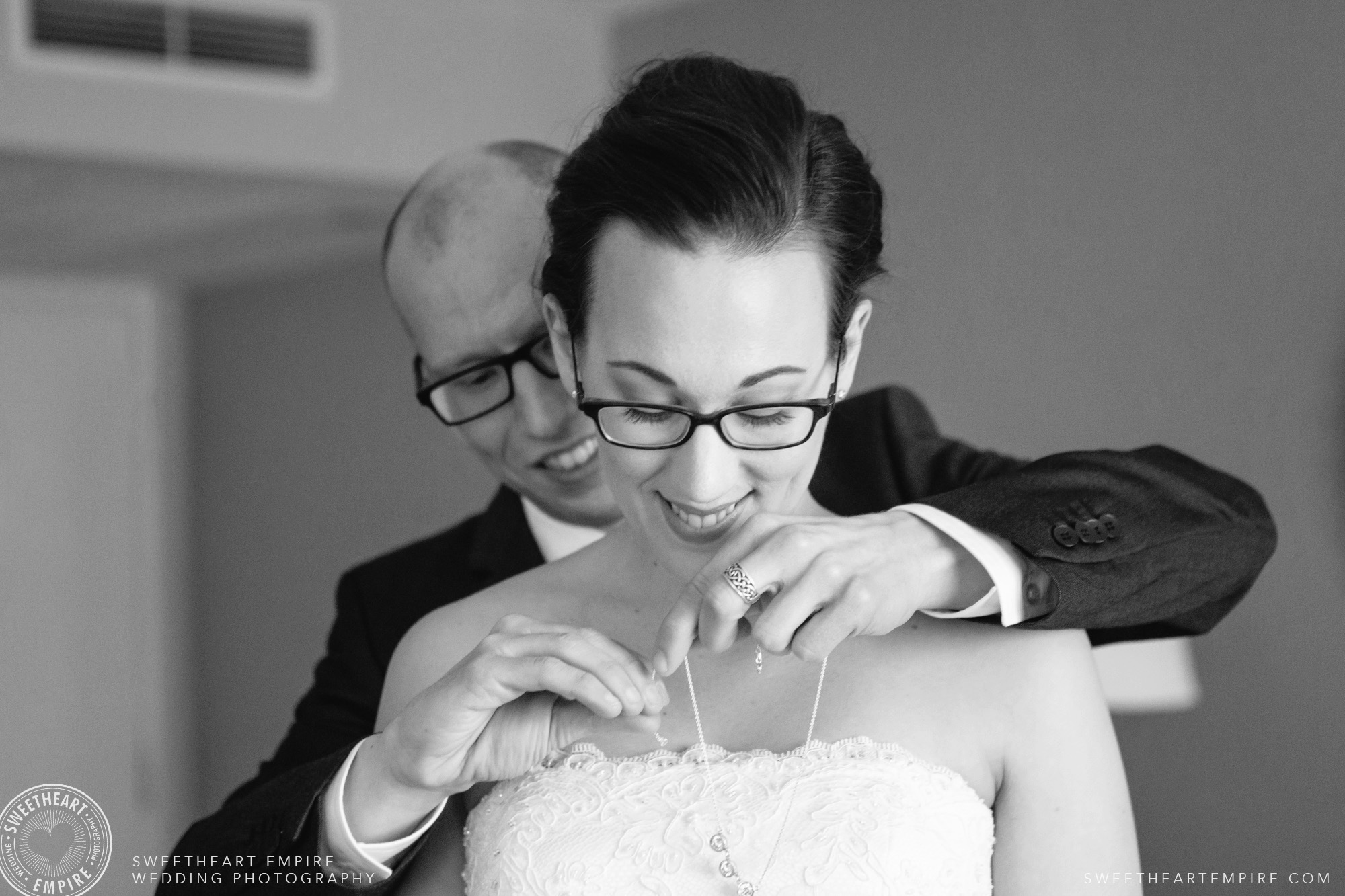 The groom helping the bride put on her necklace; Toronto Reference Library Wedding