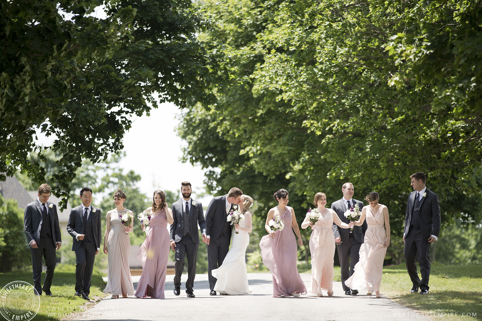 Bride and groom kiss while walking with their bridal party, Oakville Golf Club Wedding