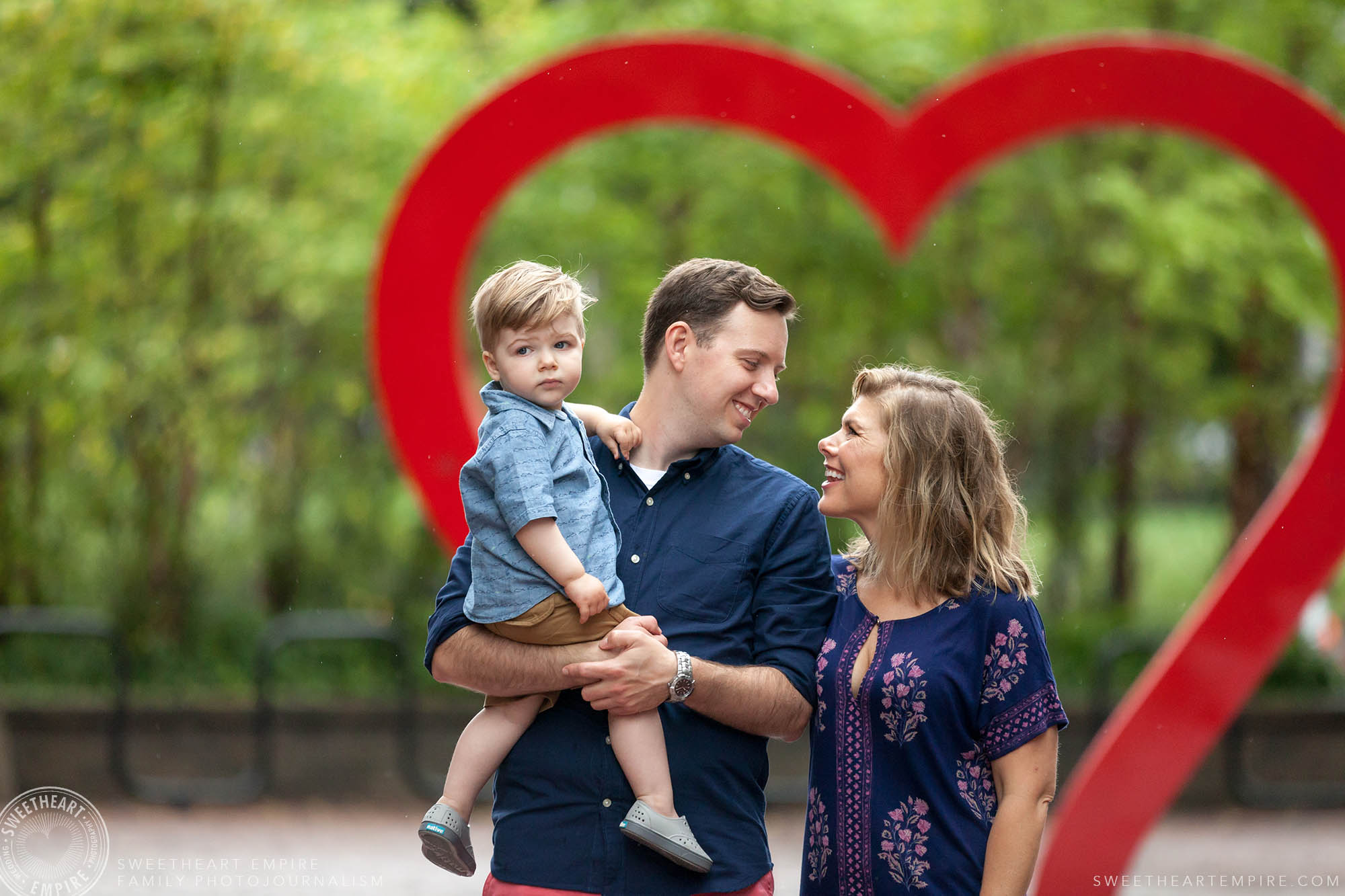 Mom and dad share a loving look while walking with son in front of oversized heart, Distillery District Family Photography