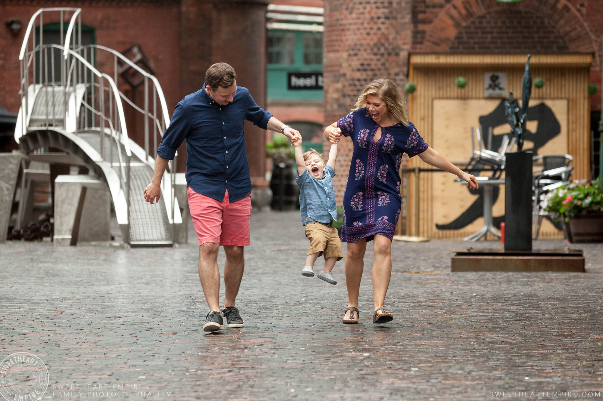 04_Laughing mom and dad swing toddler son by the arms in distillery district family session.jpg