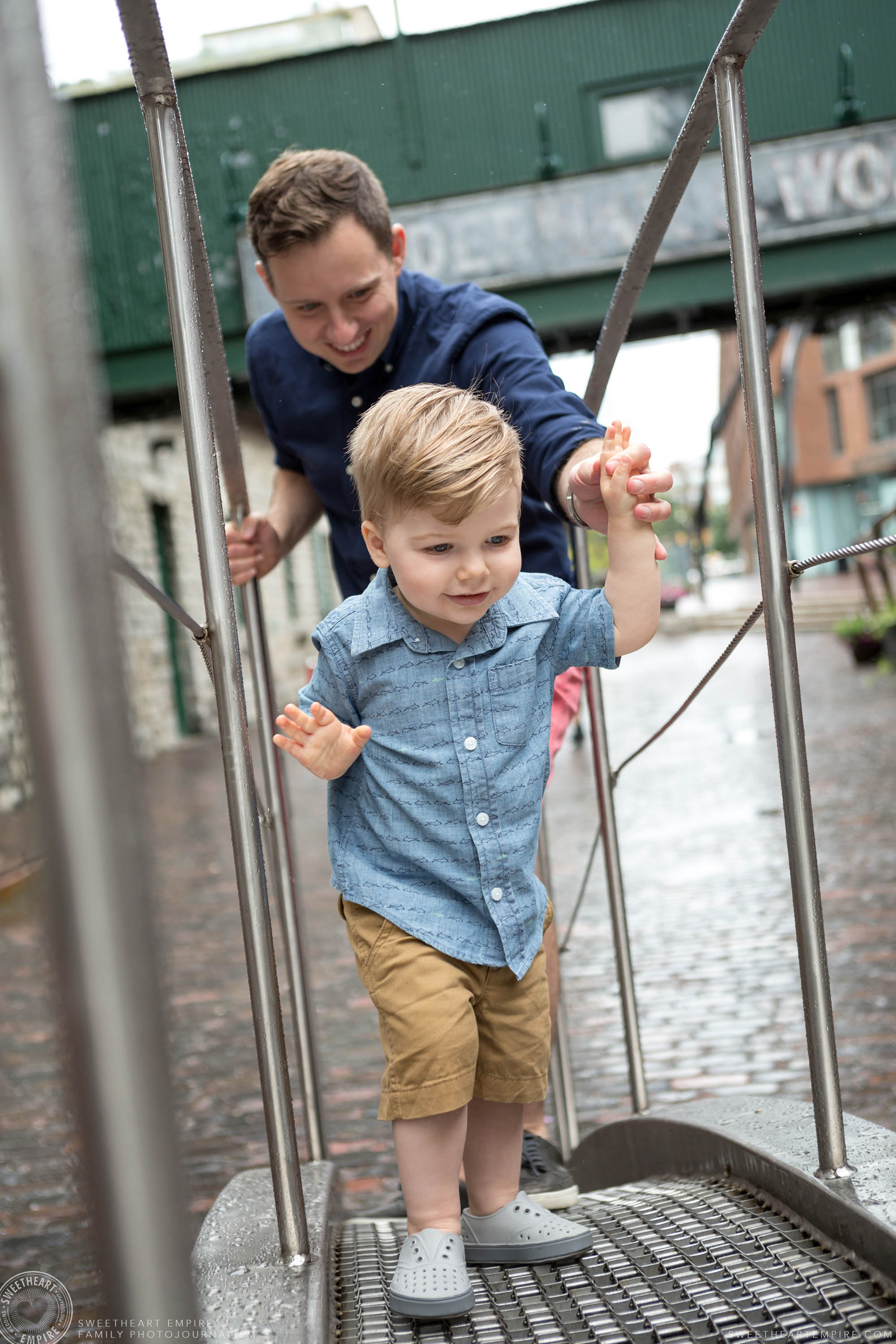 03_Toddler and father climbing sculptures in toronto distillery district.jpg