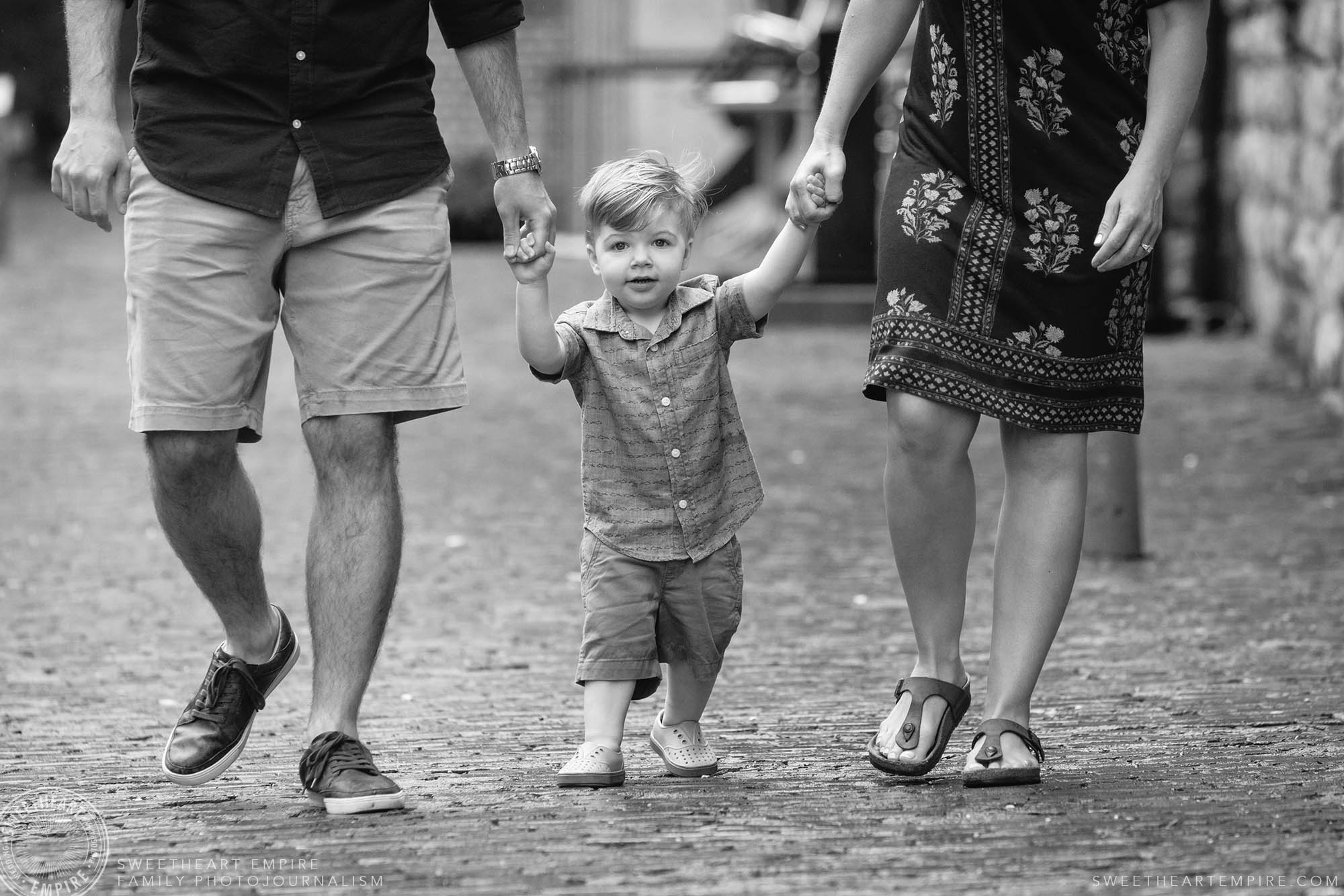 05_Sweet toddler holding his dad and moms hands in the distillery district.jpg