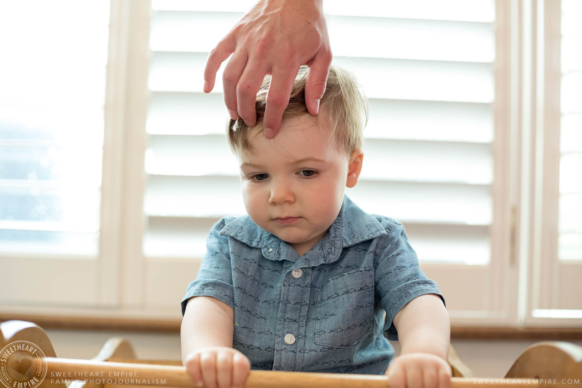15_Fathers hand fixing toddlers hair while the child concentrates on rocking the rocking hourse.jpg