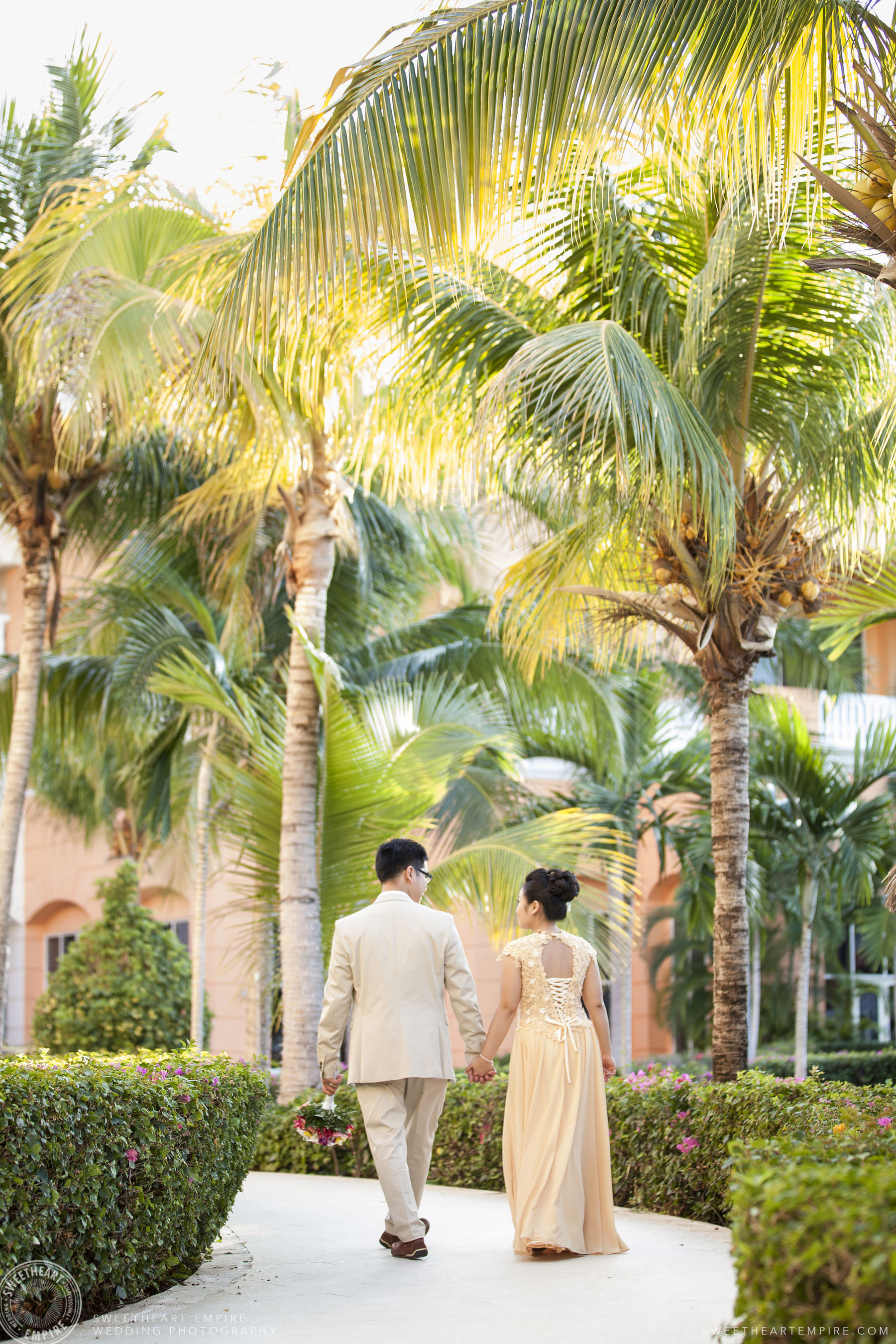 Bride and groom walking together; Iberostar Grand Hotel Rose Hall, in Montego Bay, Jamaica
