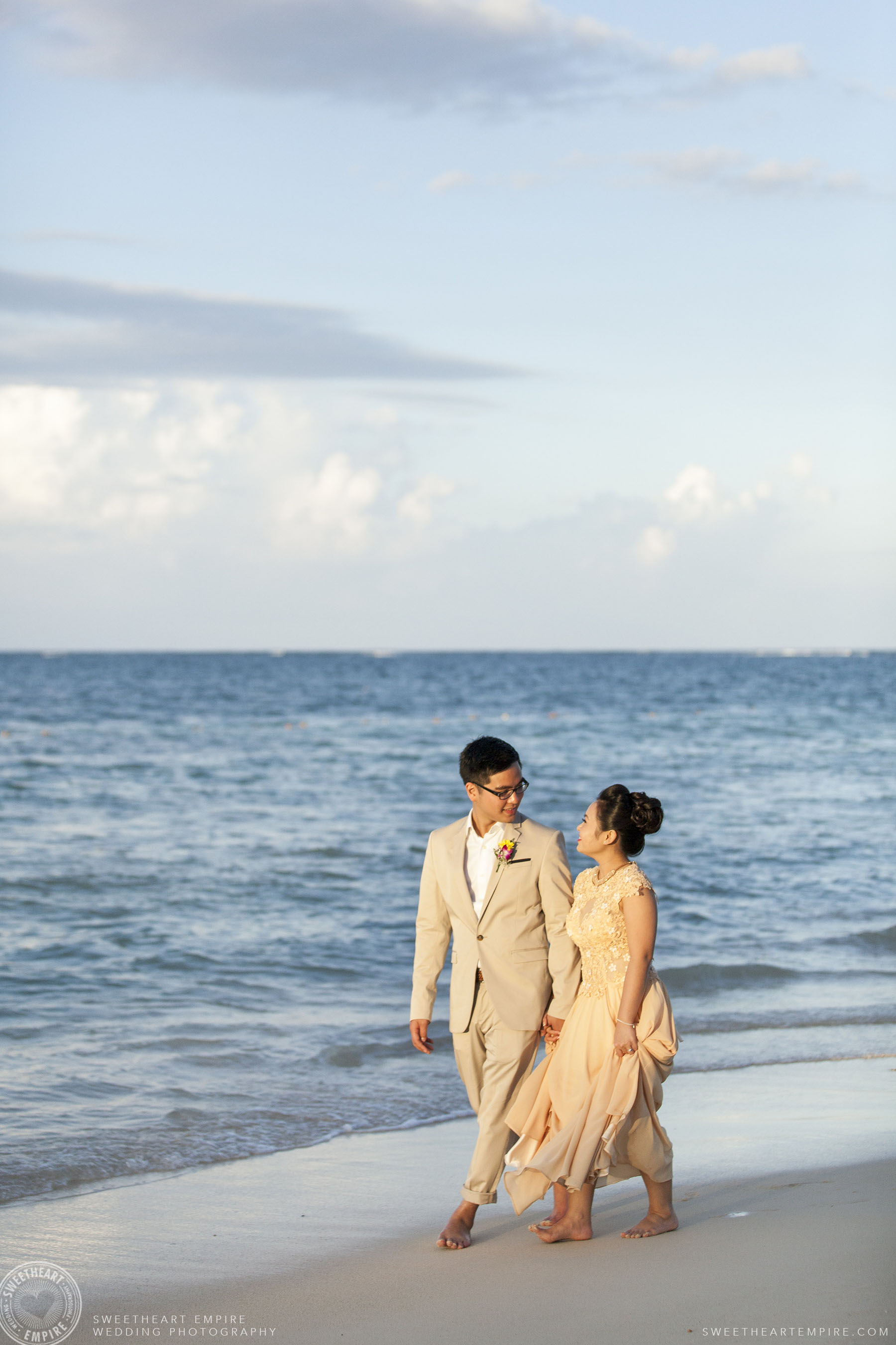 Bride and groom walking on the beach; Iberostar Grand Hotel Rose Hall, in Montego Bay, Jamaica