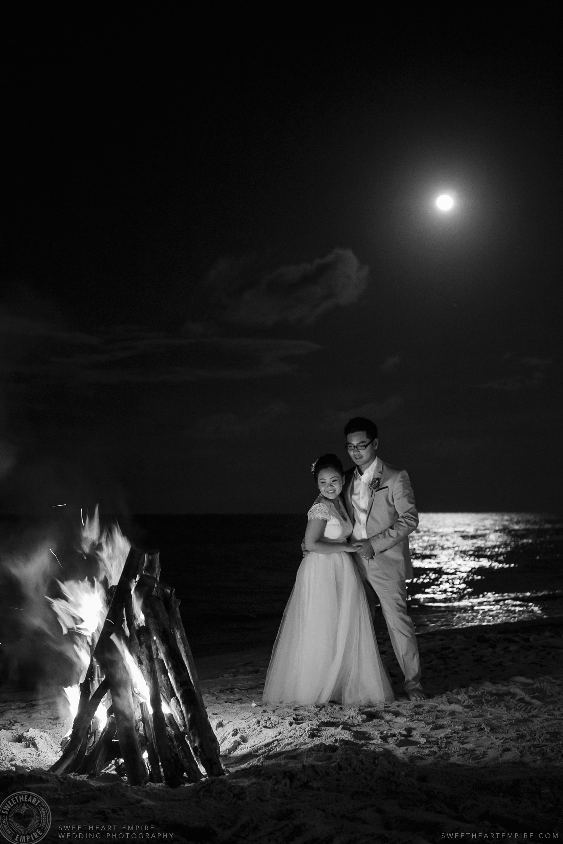 Bride and groom on the beach at night under the full moon at Iberostar Grand Hotel Rose Hall, in Montego Bay, Jamaica