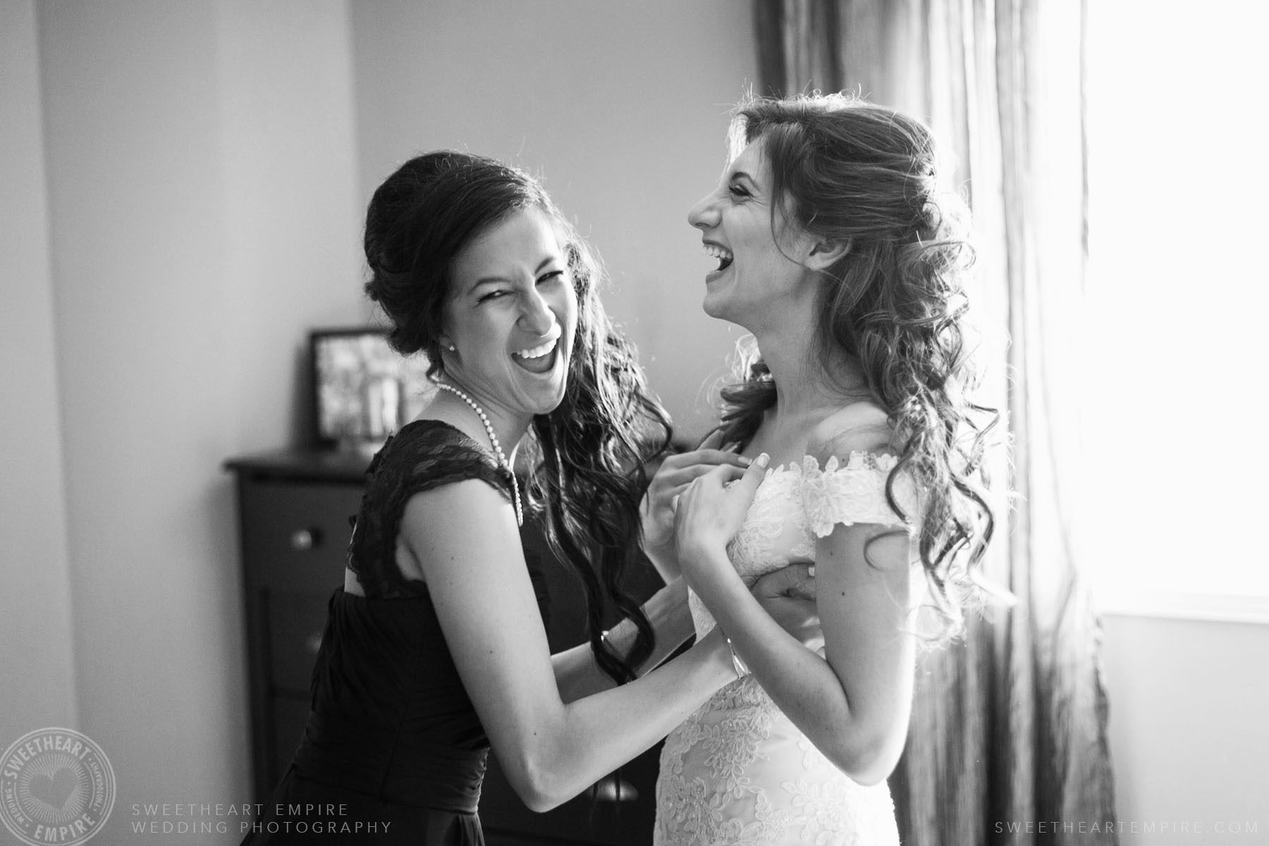 Bride getting help from her bridesmaid while getting dressed; Eagles Nest Golf Club Wedding Photos