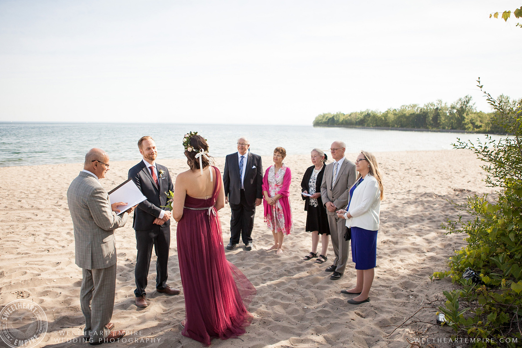 Family members look on as bride and groom exchange their vows, Toronto Island Elopement