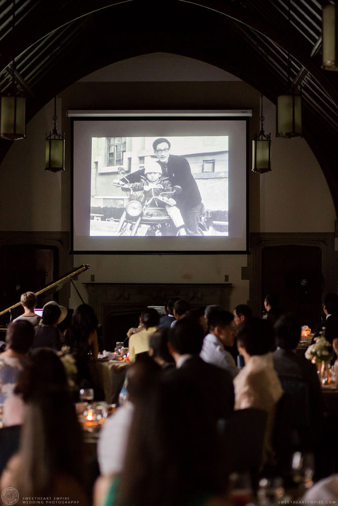 Guests watching a video of bride and groom during reception, Hart House University of Toronto Wedding