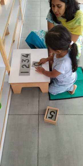 Child practicing the sandpaper numbers