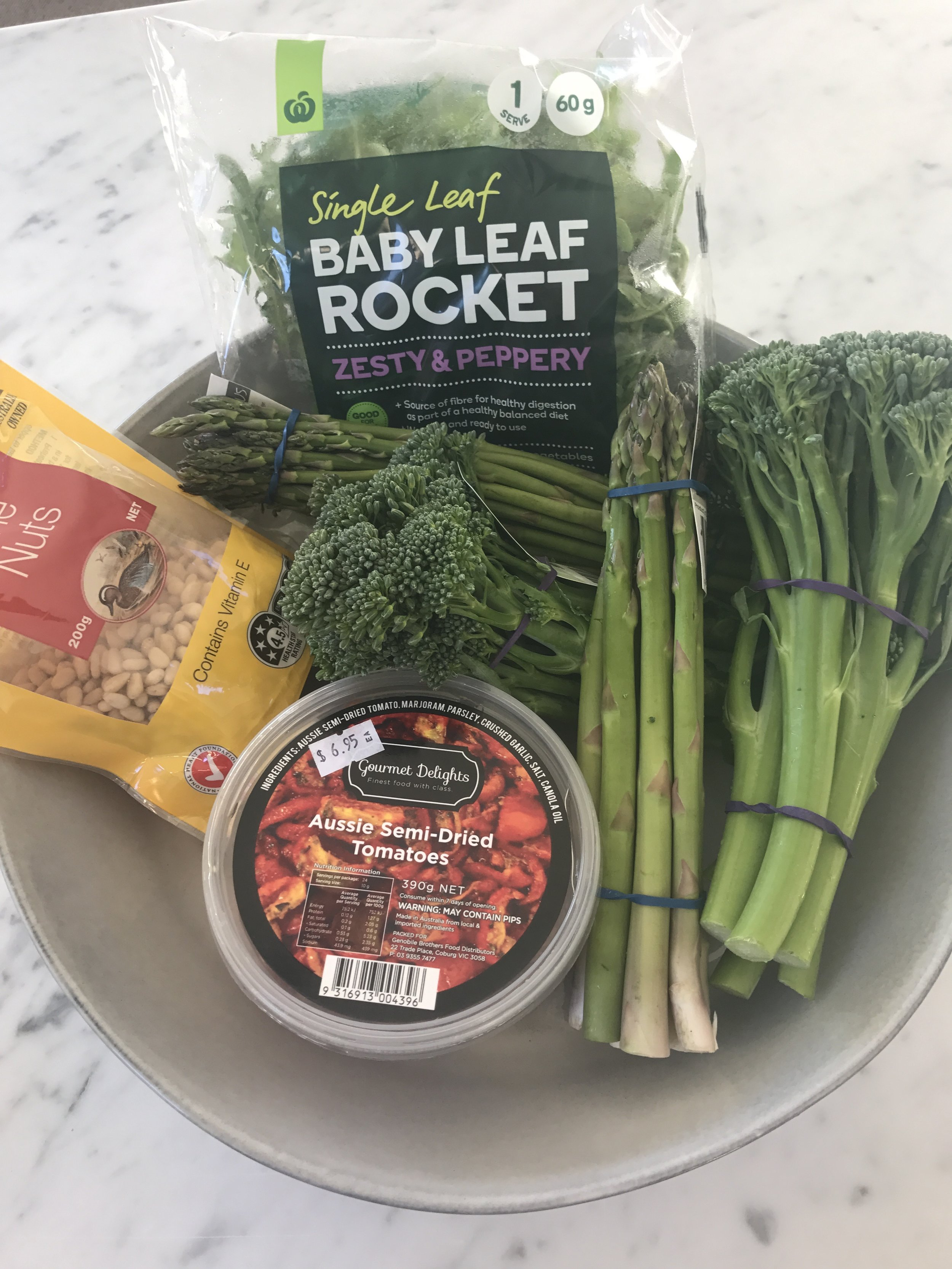Heat coconut oil, or any oil in wok or pan. Stir fry chopped asparagus and broccolini for 2 minutes. In a separate pan, toast pinenuts.  Remove both from heat. Place all ingredients in a bowl and serve.