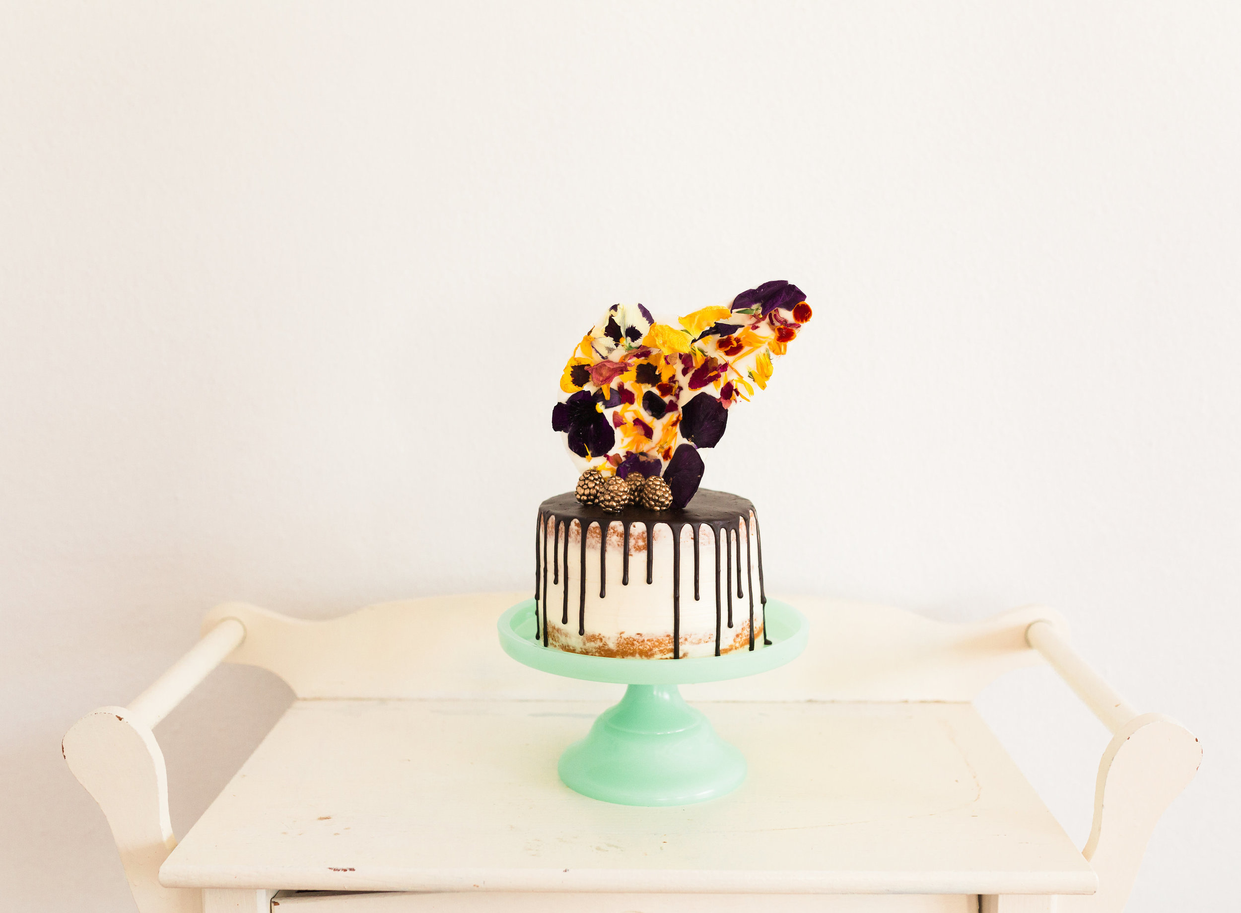 Semi-naked cake with a chocolate ganache drip, gold dusted berries, and edible flower chocolate shard. Photo:  Yasmin Roohi