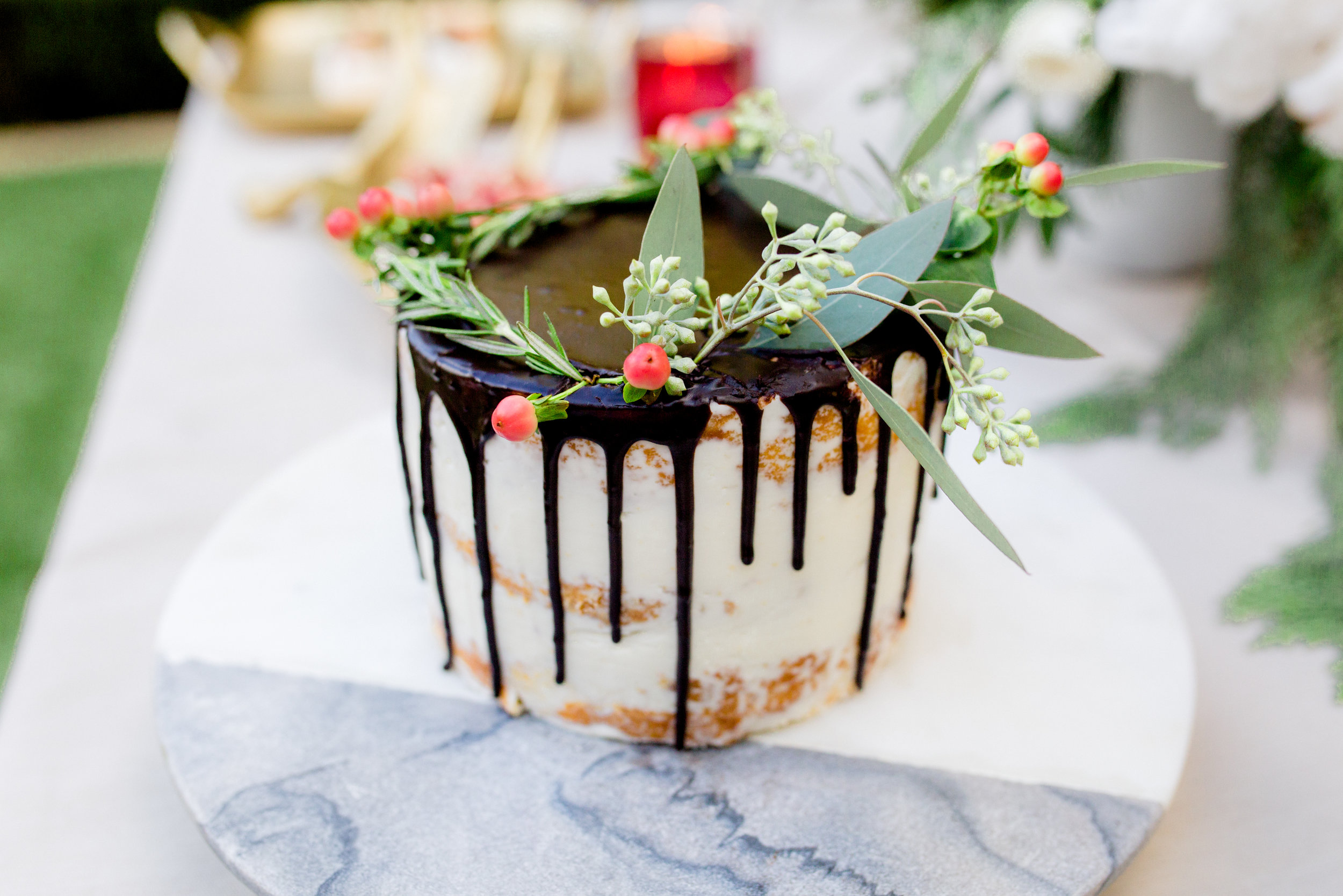 Semi-naked chocolate drip cake decorated with fresh florals. Photo:  Yasmin Roohi