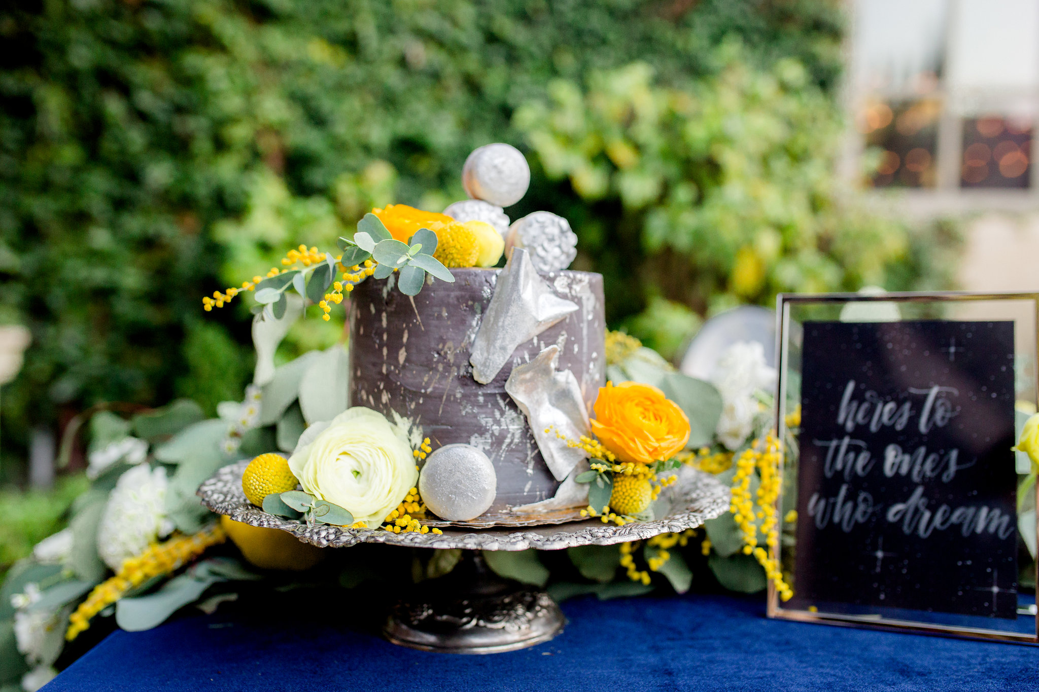 Buttercream frosted cake with silver splatter, silver macarons, silver dusted chocolate shards, and fresh florals. Photo:  Yasmin Roohi